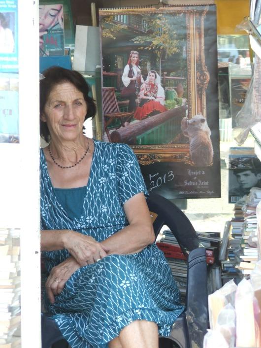 בעלת חנות ספרים בפתח חנותה